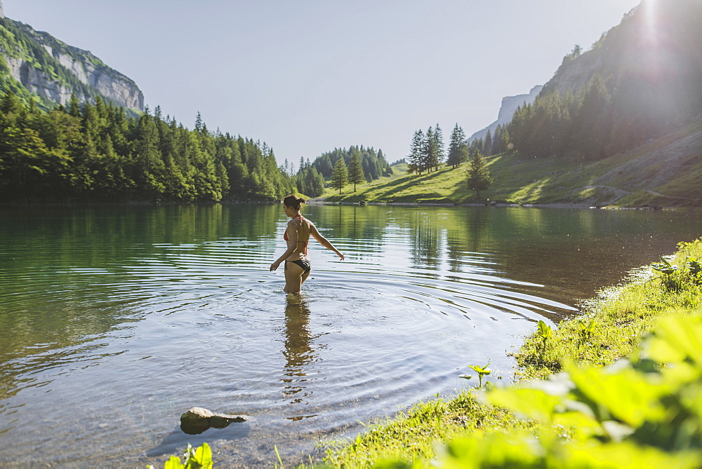 Woman swimming in Seealpsee lake in Appenzell Alps, Switzerland