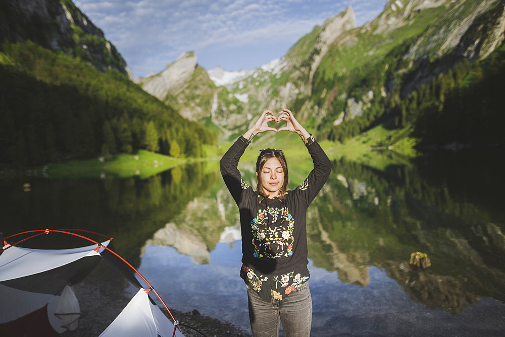 Woman making heart hand sign by Seealpsee lake in Appenzell Alps, Switzerland