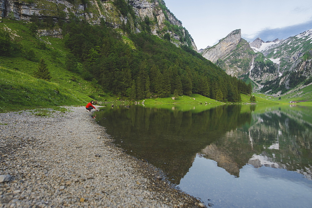 Woman crouching by Seealpsee lake in Appenzell Alps, Switzerland