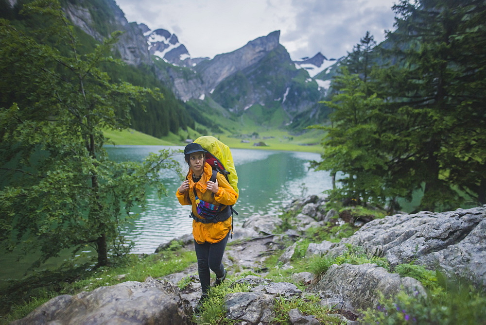 Woman wearing yellow hiking by Seealpsee lake in Appenzell Alps, Switzerland