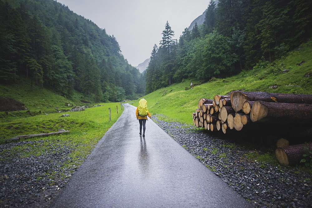 Woman hiking on road in Appenzell Alps, Switzerland