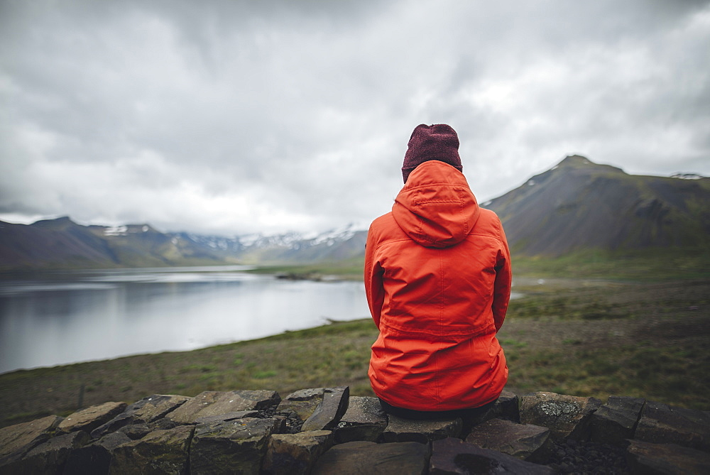Woman wearing red raincoat sitting by fjord in Snufellsnes, Iceland