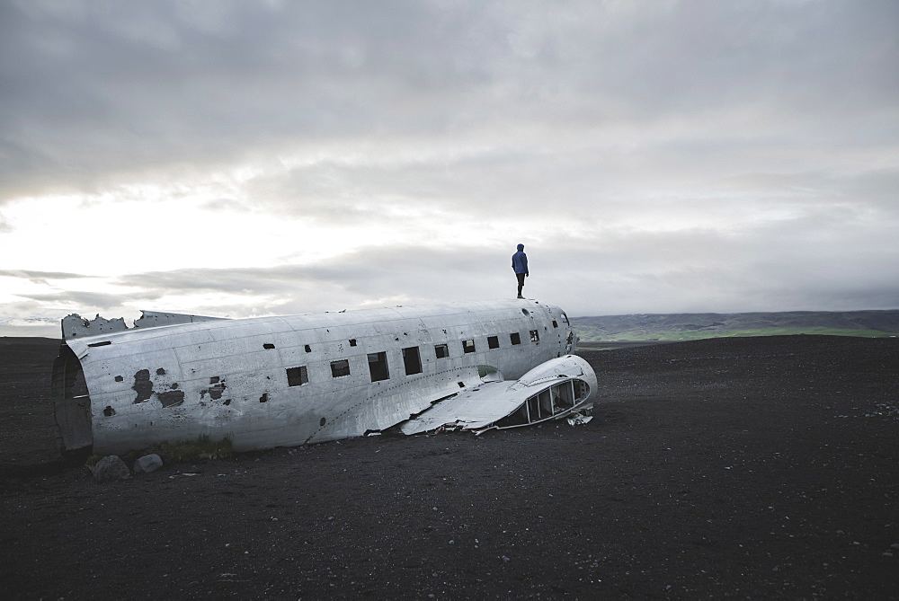Man standing on abandoned airplane in black sand desert