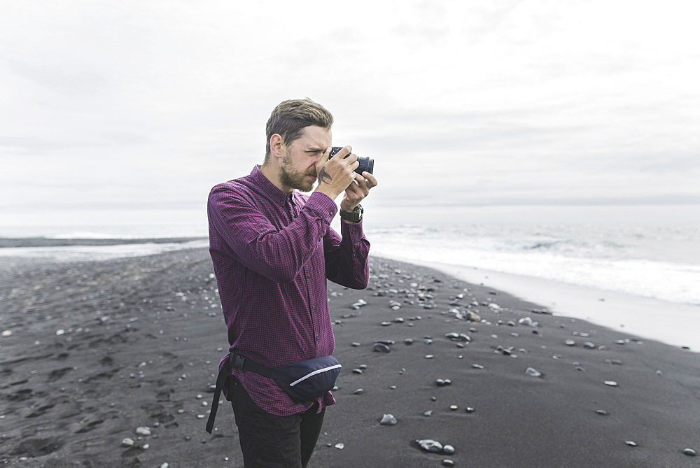 Man taking photograph on beach in Iceland