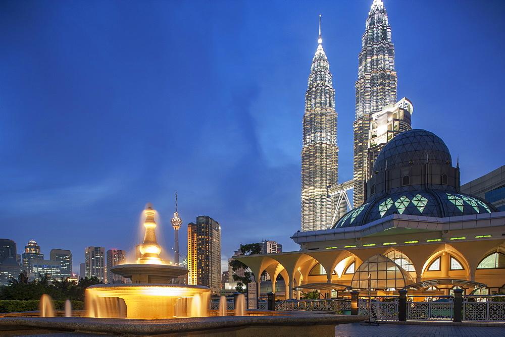Petronas Towers behind mosque at night in Kuala Lumpur, Malaysia
