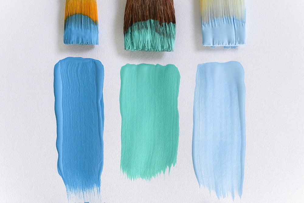 Paintbrushes and blue brushstrokes