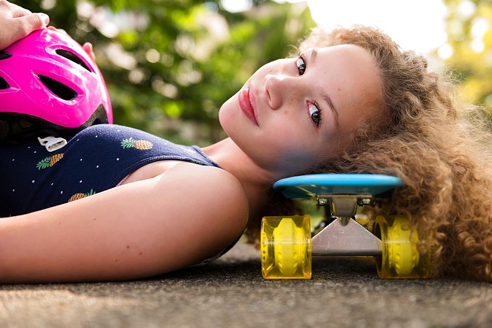 Girl lying on skateboard