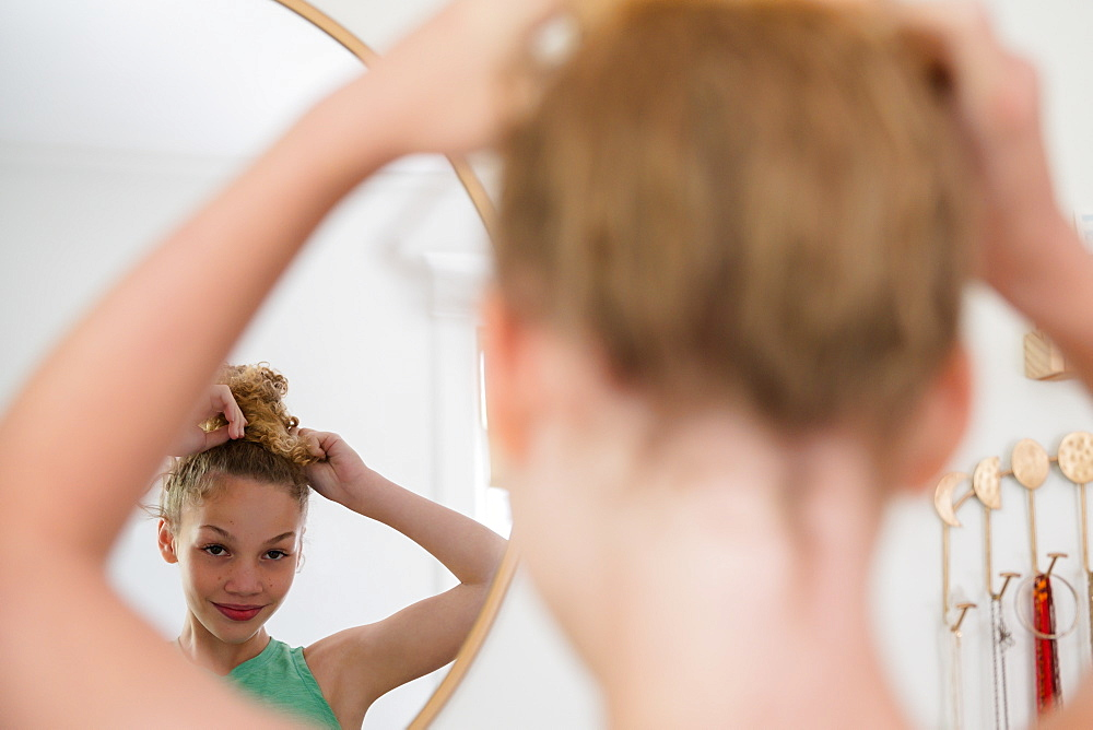 Girl doing hair in mirror