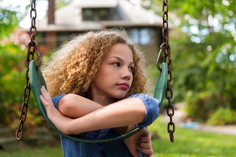 Girl leaning on swing