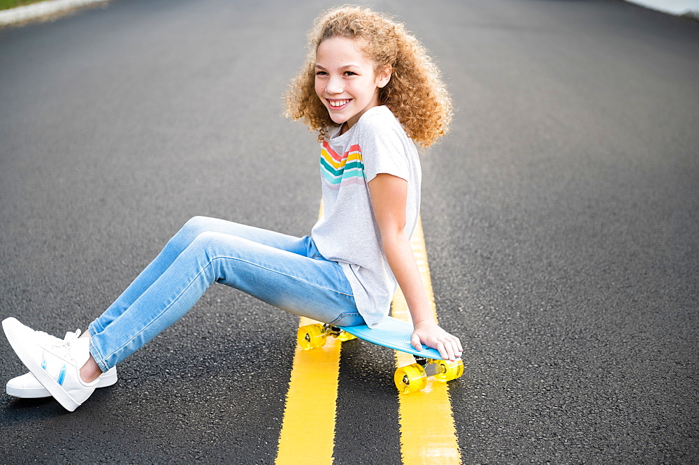 Girl sitting on skateboard on road