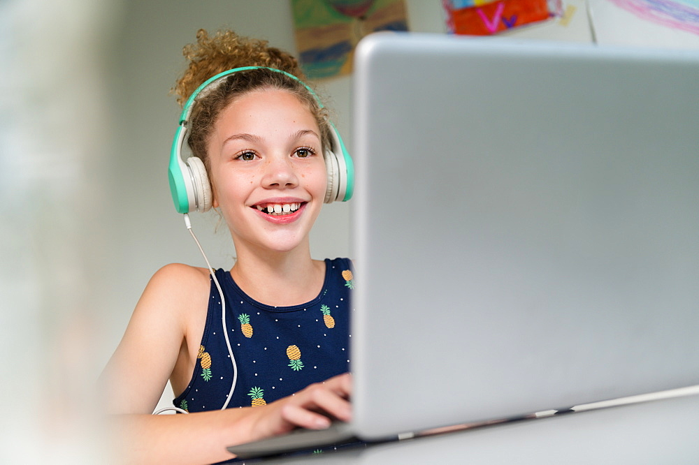 Smiling girl wearing headphones using laptop