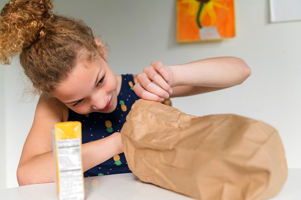 Girl looking into brown paper bag