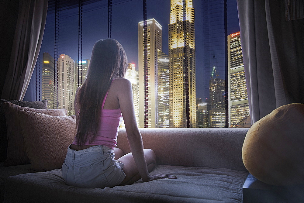 Woman sitting on sofa looking out window in Singapore, South East Asia