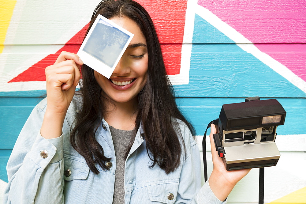 Smiling woman holding photograph and Polaroid camera