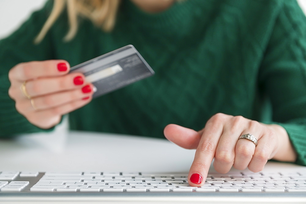 Woman holding credit card and typing on keyboard