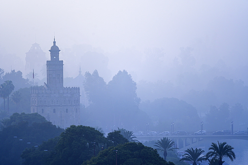 Torre del Oro amongst trees and fog in Seville, Spain