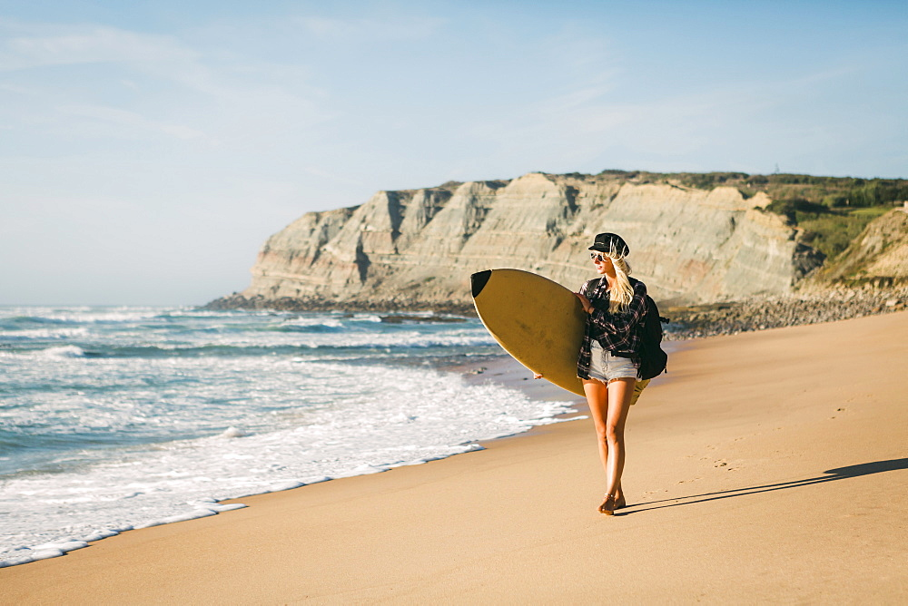 Woman holding surfboard on beach