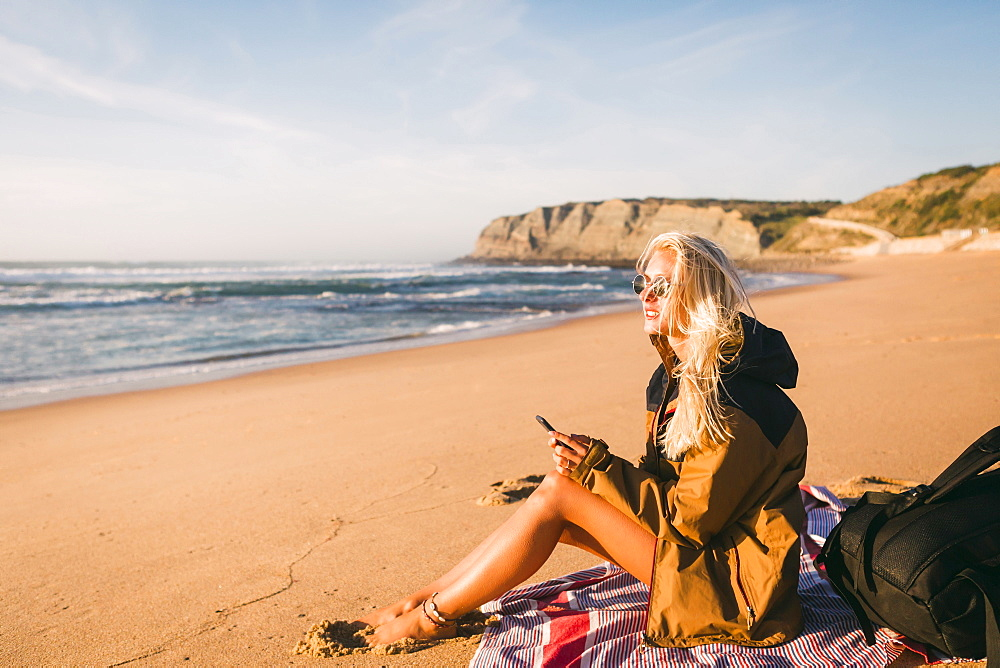 Woman holding phone sitting on beach