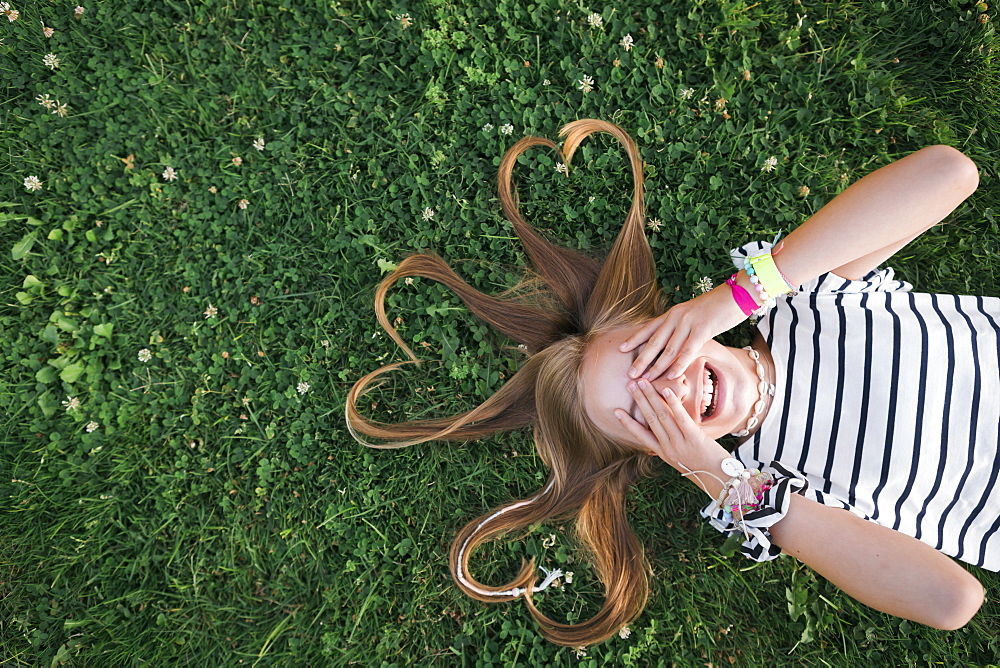 Girl with her hair in heart shapes lying on grass