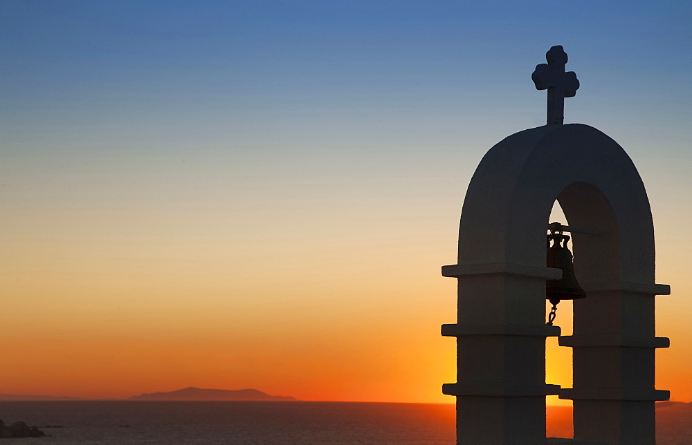 Silhouette of bell tower at sunset in Mykonos, Greece