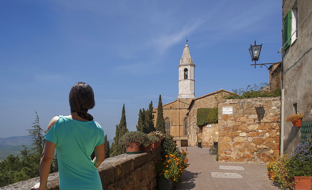Woman by stone wall and church in Tuscany, Italy
