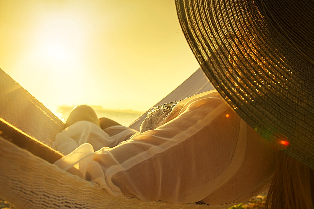 Woman wearing hat on hammock at sunset