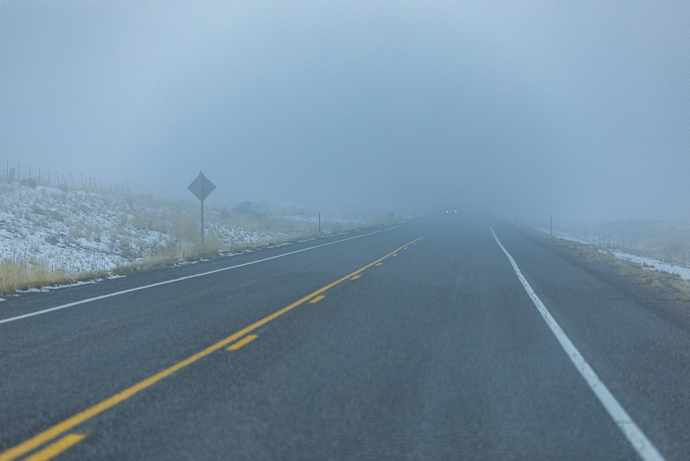 Road by snow in fog, Mountain Home, Idaho, USA