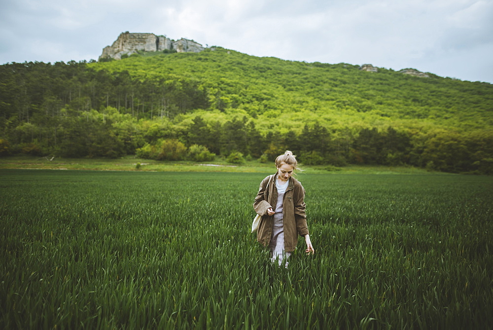 Woman wearing jacket walking in field in Crimea, Ukraine