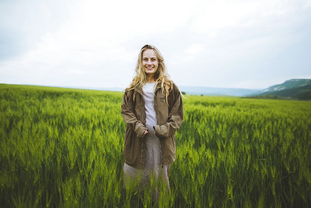 Smiling woman wearing jacket in field in Crimea, Ukraine