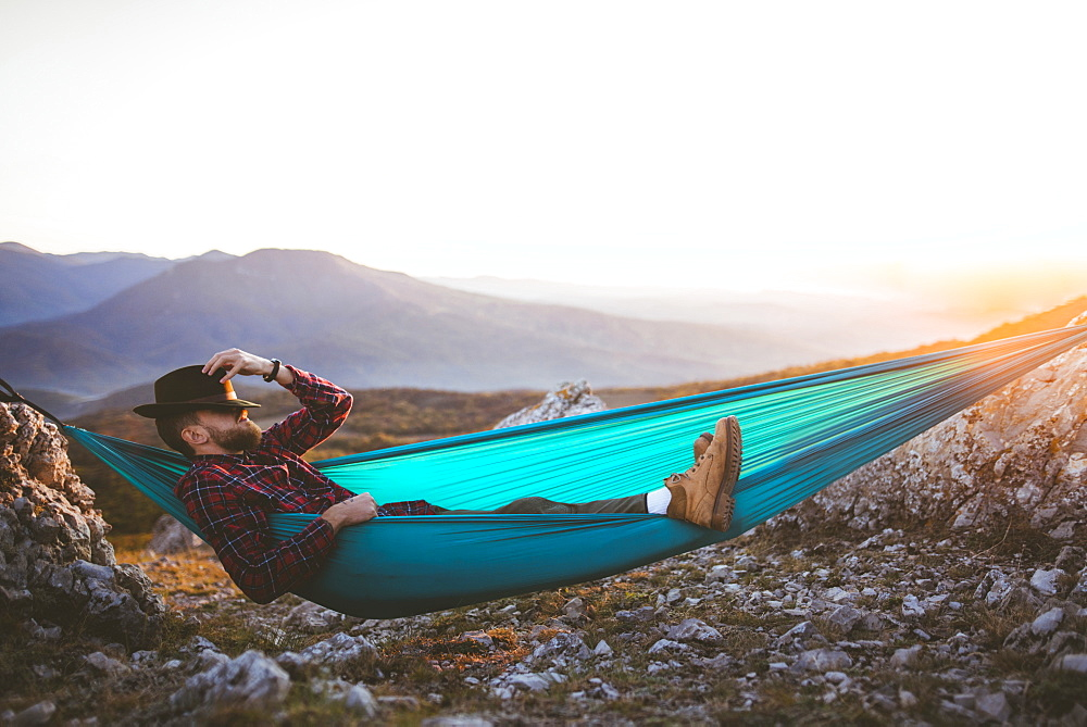 Man sleeping on hammock in mountain range
