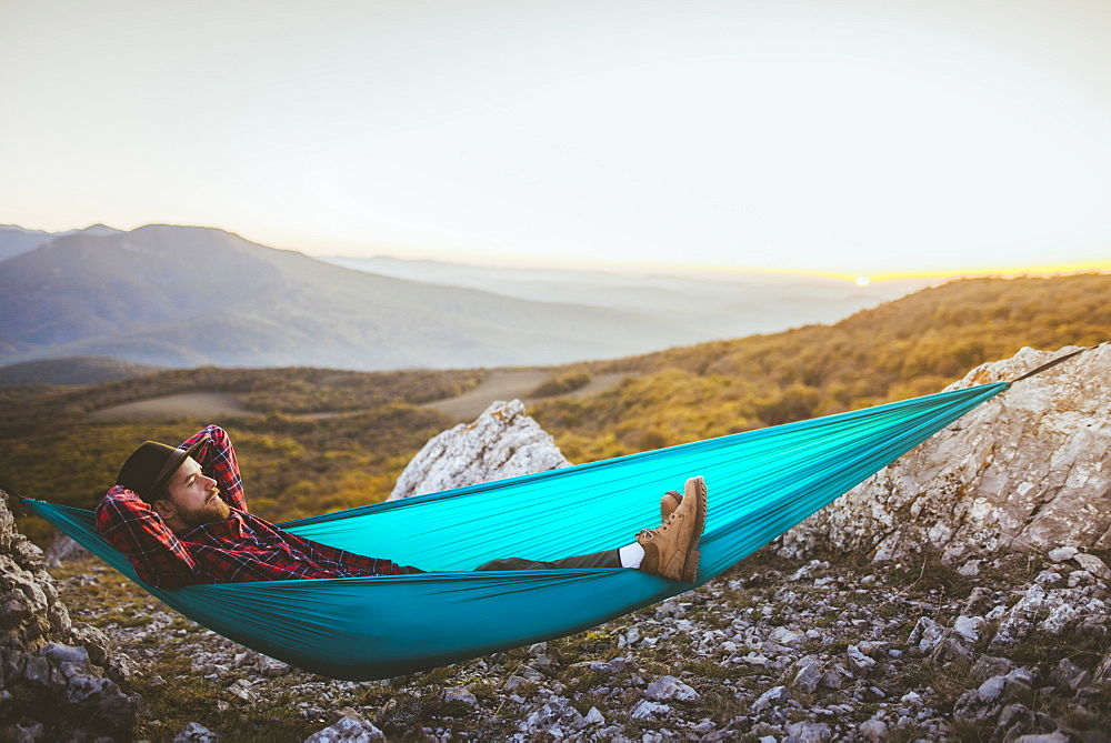 Man lying on hammock in mountain range