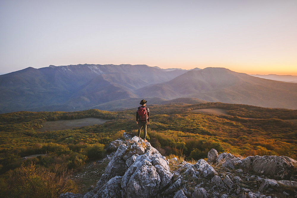 Man on rock by mountains at sunset