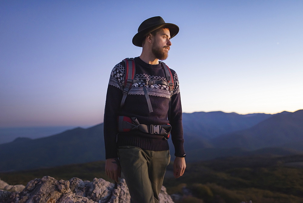 Man against mountain range at sunset