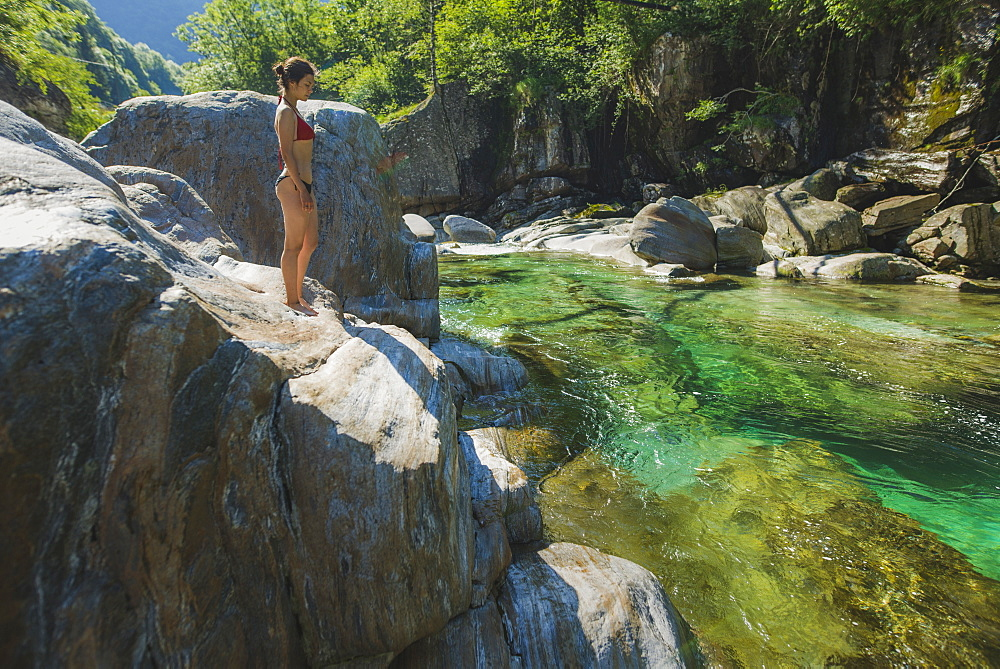Woman wearing bikini on rock by river