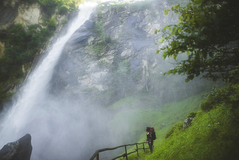 Woman on grass by waterfall