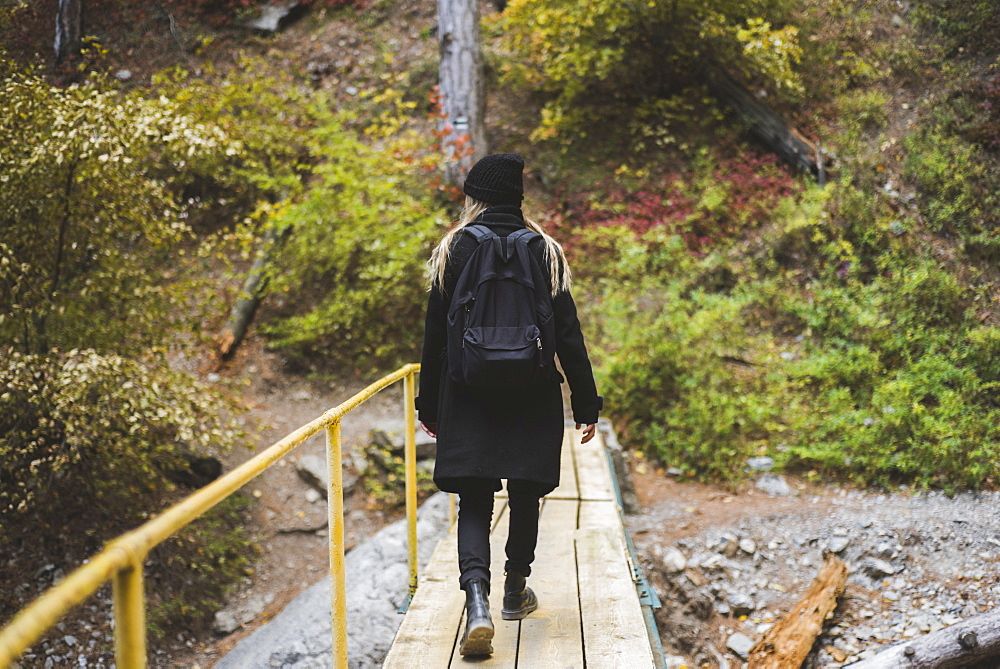 Young woman walking across bridge in forest