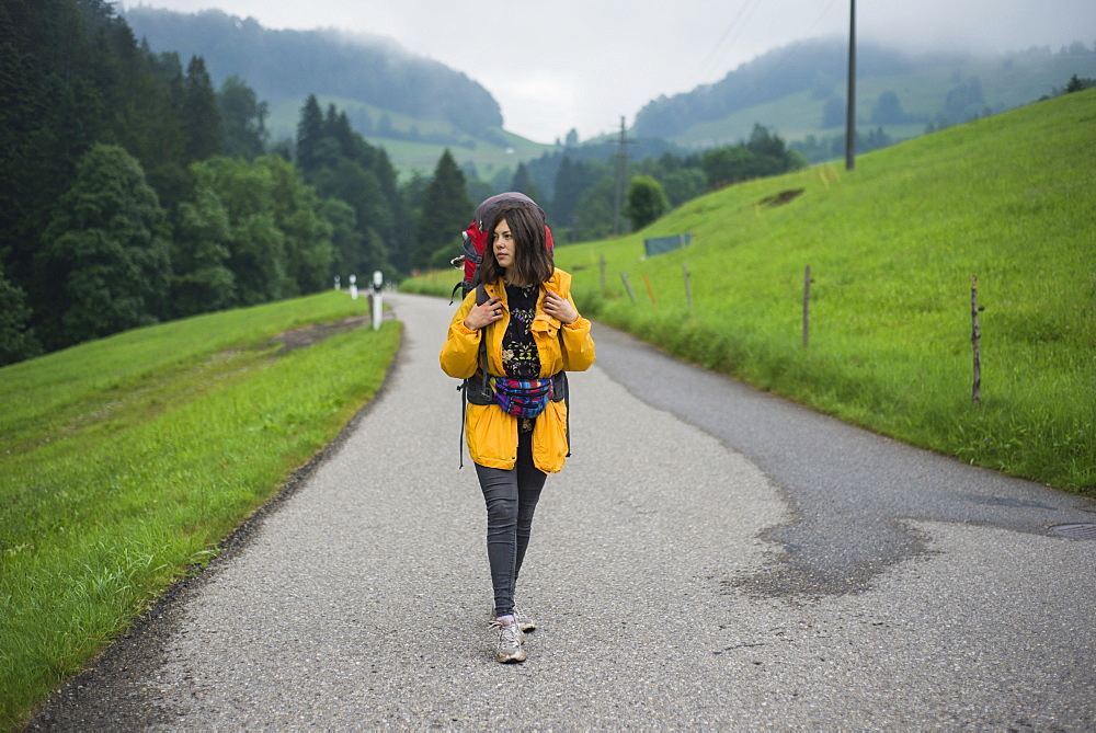 Young woman with yellow jacket and backpack walking along country road