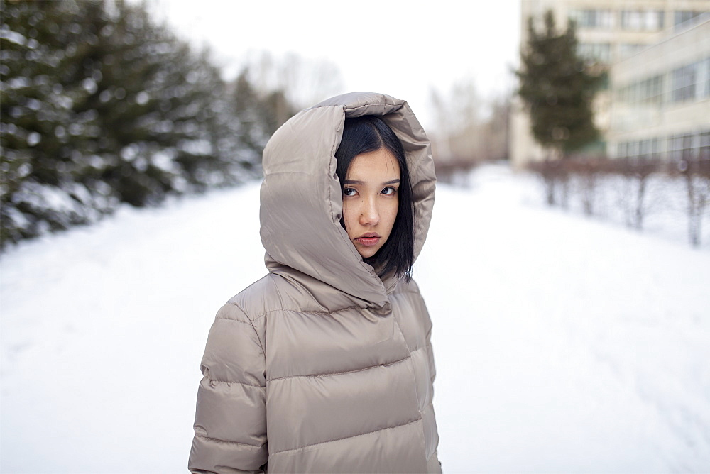 Young woman in hooded jacket during winter