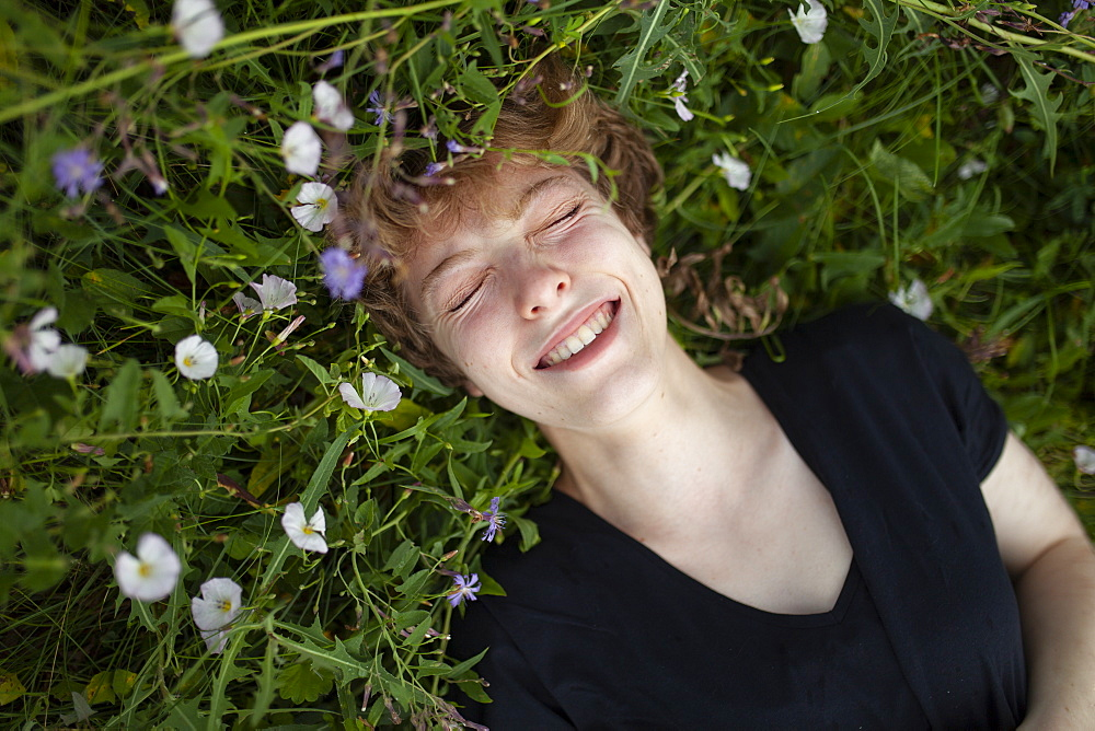 Smiling young woman lying in grass