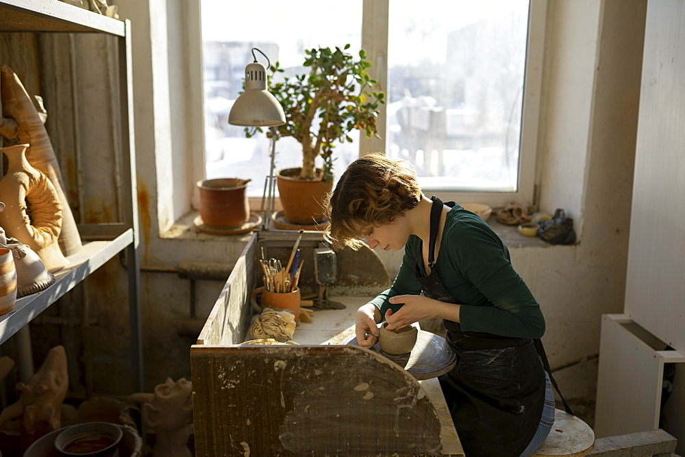 Potter working at desk in workshop