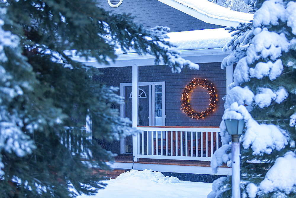 Illuminated Christmas wreath on house during winter