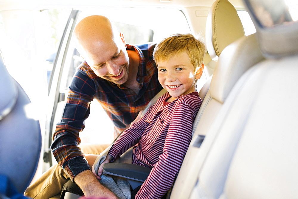 Boy smiling as his father buckles his seat belt