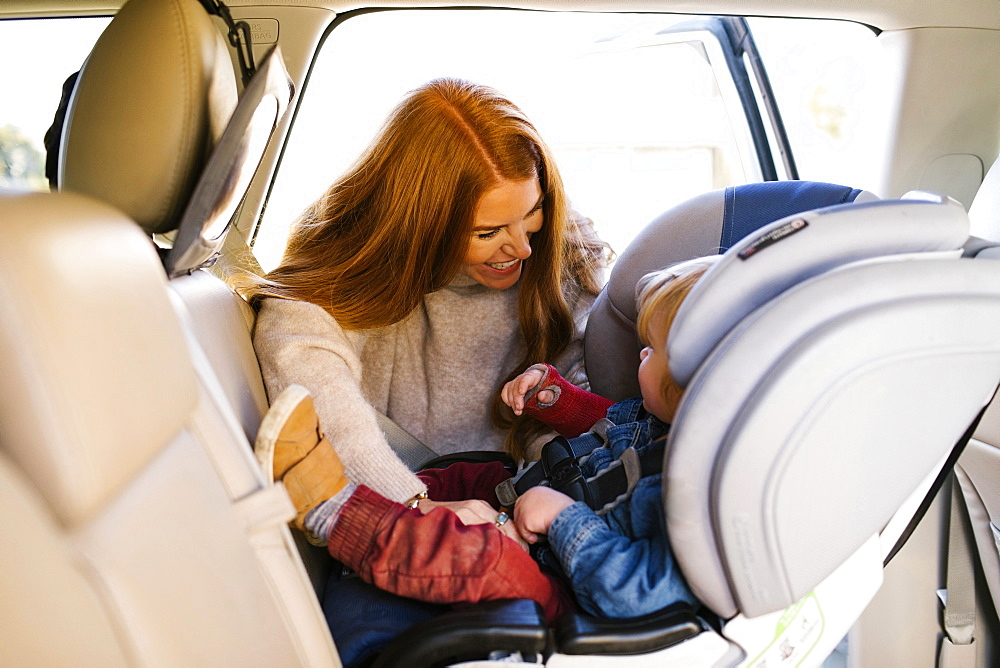 Woman smiling at son sitting in car set - 1178-28592