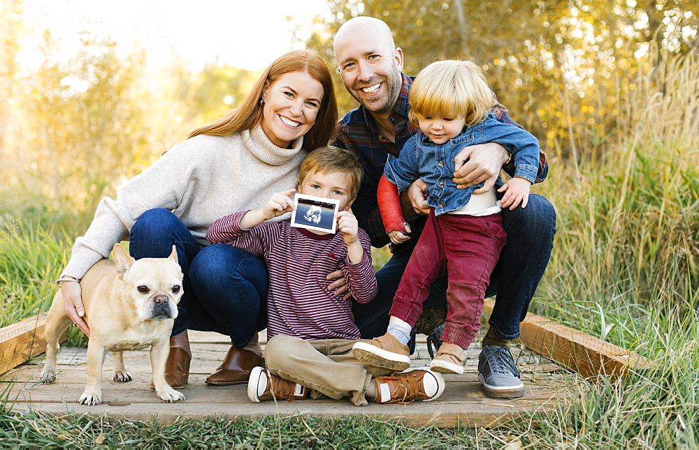 Smiling family with ultrasound photograph and pet dog on forest boardwalk - 1178-28594