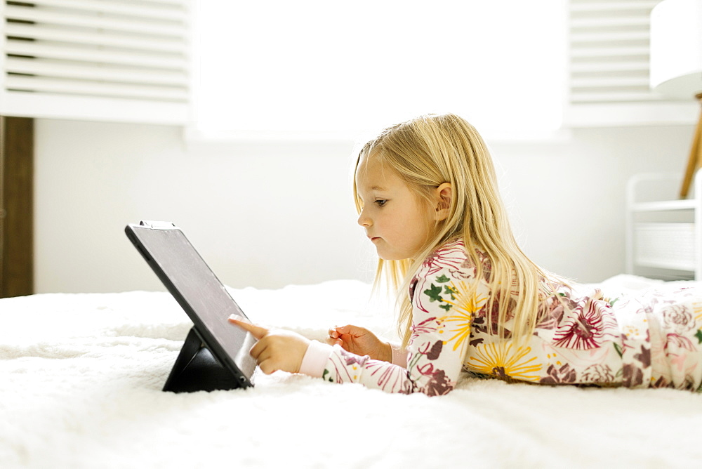 Girl in pajamas using digital tablet while lying on bed