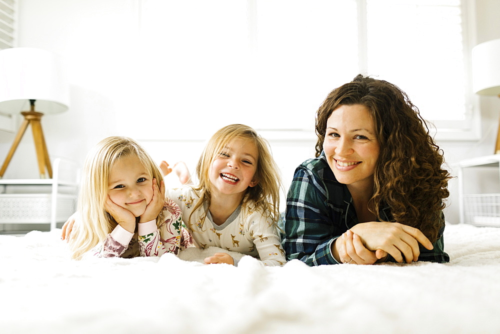 Mother and daughters lying on bed in pajamas