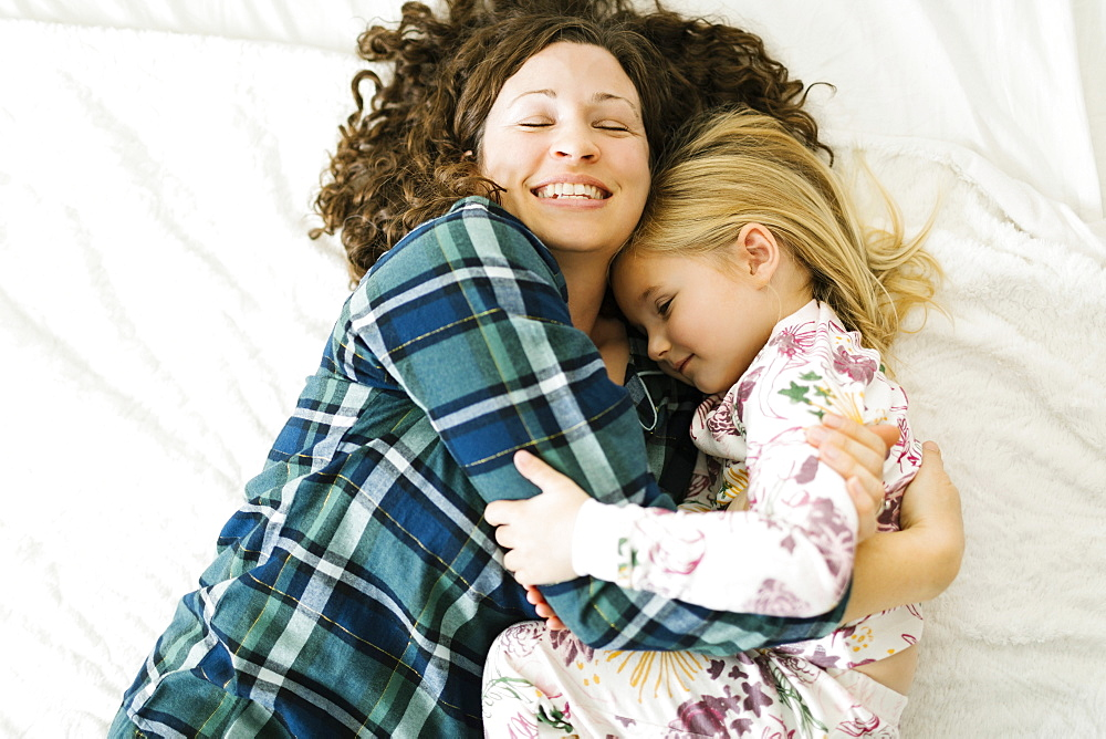High angle view of mother and daughter in pajamas lying on bed