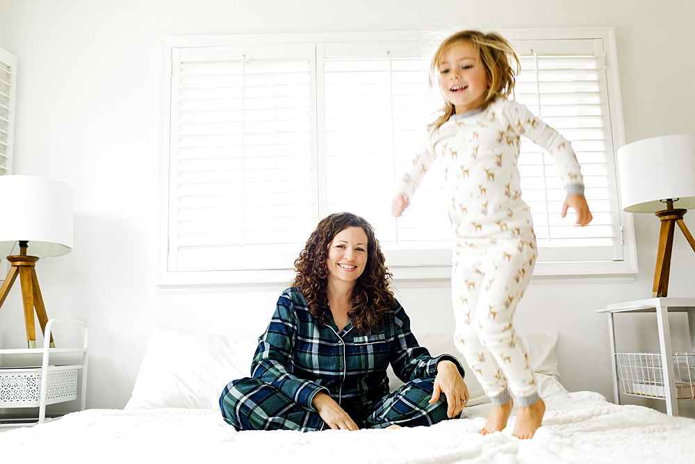 Girl jumping on bed and her smiling mother