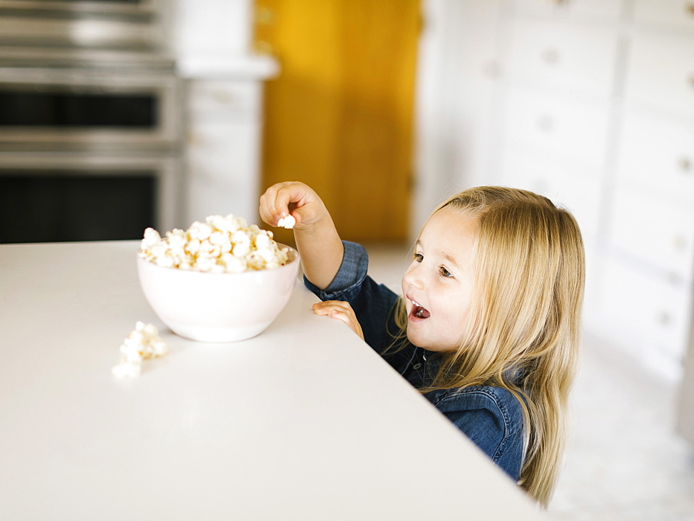 Girl taking popcorn from bowl on kitchen counter