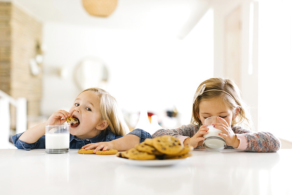 Girls eating milk and cookies